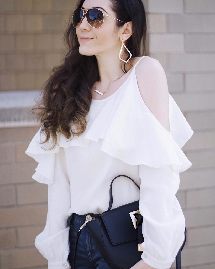 The Style Theory Collective Camel Coat, Moon River White Ruffle Blouse, Express Jeans, Steve Madden Black Sandals, Black Camelia Roma Black Crossbody, Kendra Scott Gold Earrings